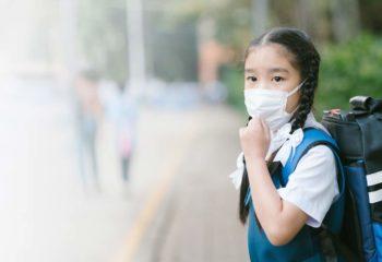 Jeune écolière portant un masque contre la pollution